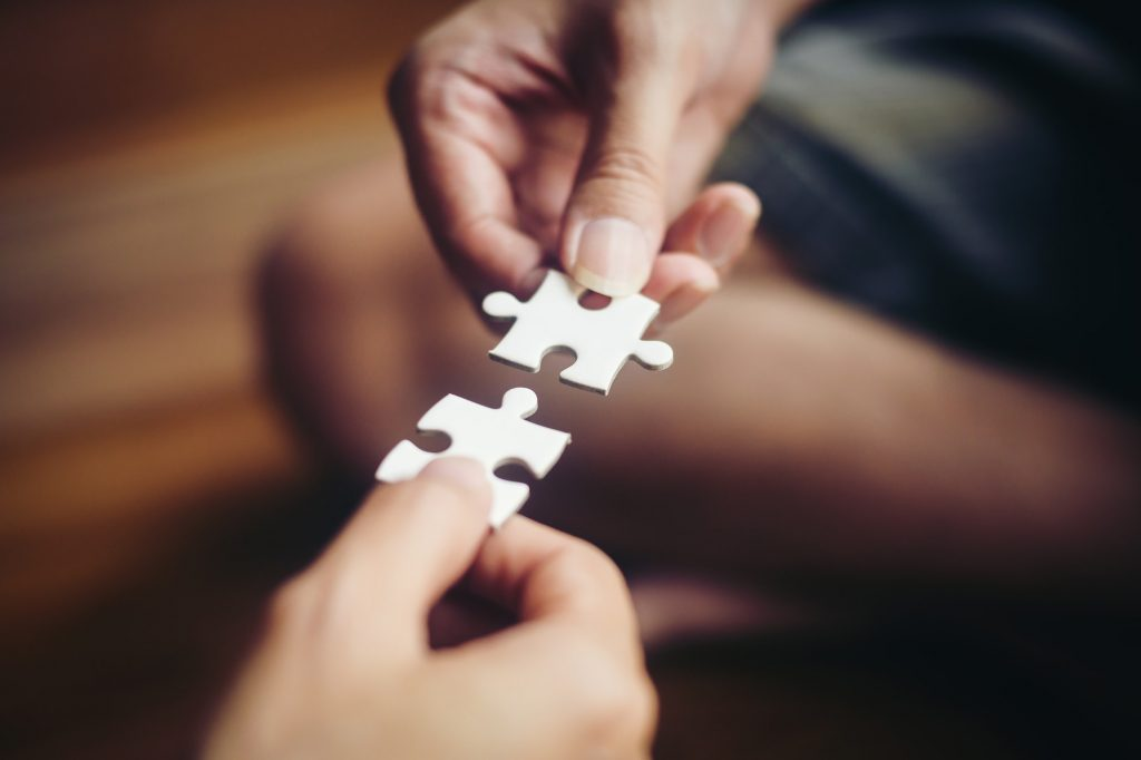 Hand holding jigsaw puzzles, Business partnership concept.